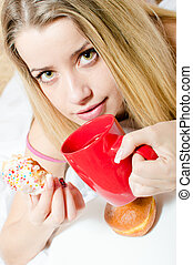 closeup portrait of charming young blond pretty woman drinking beverage from red cup & biting color glaze donut relaxing sitting in bed & looking at camera