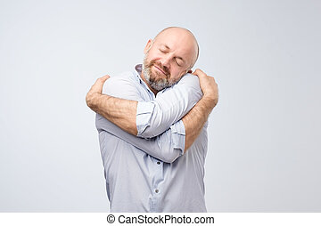 Closeup portrait of confident smiling man holding hugging...