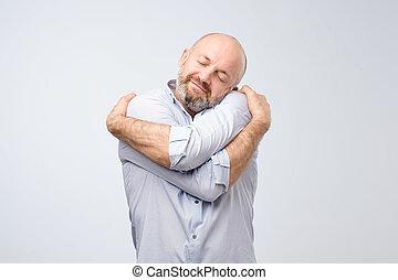 Closeup portrait of confident smiling man holding hugging ...