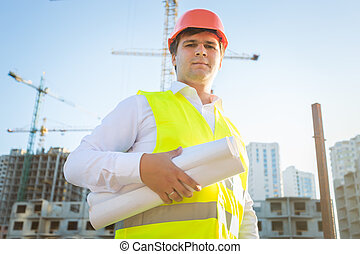 portrait of construction manager posing with blueprints