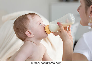 Closeup portrait of cute baby boy drinking milk from bottle that mother is holding