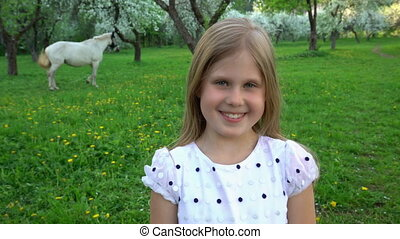 Closeup portrait of beautiful cute caucasian little girl smiling while looking at camera. Pretty girl send air kiss at camera. White horse visible inn background. Static shot