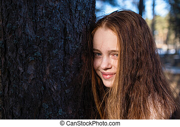 Closeup portrait of cute girl with long bright red hair in the pine park.