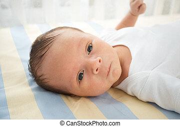 Closeup portrait of cute newborn baby lying in bed