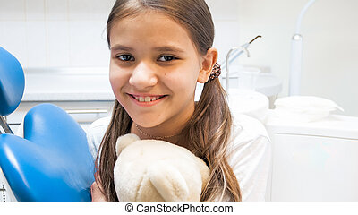 Closeup portrait of cute smiling girl with teddy bear sitting in dentist chair