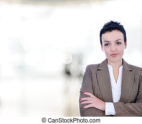 Closeup portrait of cute young business woman smiling in modern bright building