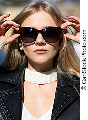 Closeup portrait of elegant blonde model with long hair wearing sunglasses posing in sun light