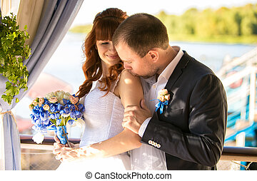 portrait of elegant groom kissing bride at shoulder at summer te