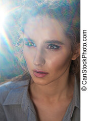 Closeup portrait of fashionable blonde model with natural makeup posing with sun glare