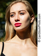 Closeup portrait of fashionable blonde model with professional makeup posing at the street