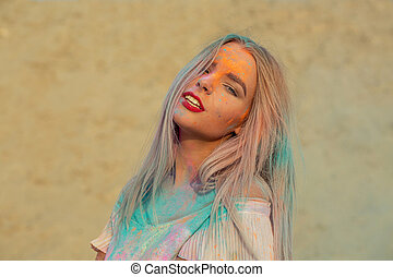 Closeup portrait of fashionable blonde model with red lips playing with orange dry paint Holi at the desert