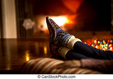 portrait of feet at woolen socks warming at fireplace in...