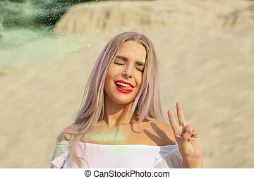 Closeup portrait of flirty blonde model playing with green dry paint Holi and showing peace sign