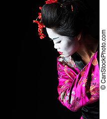 Closeup portrait of geisha isolated on black