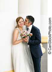 Closeup portrait of groom kissing bride in cheek at high columns