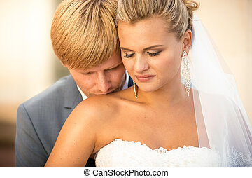 portrait of handsome groom kissing blonde bride in shoulder