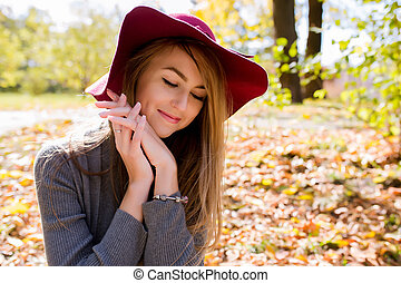 Closeup portrait of happy blonde woman with natural makeup in red hat posing at the park
