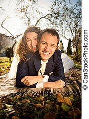 portrait of happy bride and groom embracing on grass at park