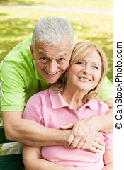 happy elderly man embracing mature woman