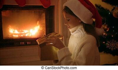 Closeup portrait of happy girl in Santa hat looking inside of glowing Christmas gift box