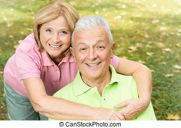 happy mature woman embracing elderly man