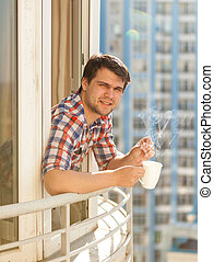 portrait of hipster guy drinking coffee on balcony