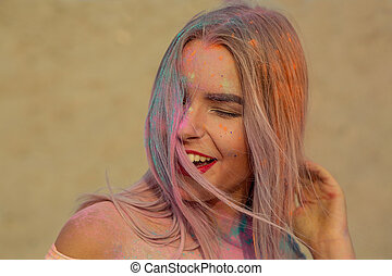 Closeup portrait of laughing blonde girl with red lips playing with orange dry paint Holi at the desert
