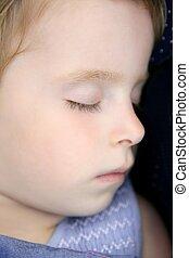 Closeup portrait of little blond child sleeping