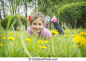 Closeup portrait of little cute girl lying with dandelions on the grass.
