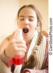 portrait of little girl with sore throat using spray