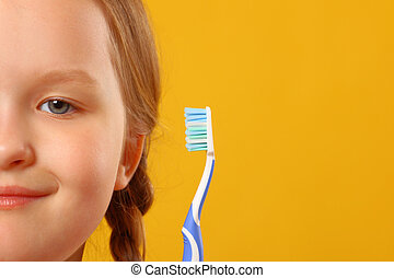 Closeup portrait of little girl's face on yellow background. holding a toothbrush. The concept of daily hygiene.