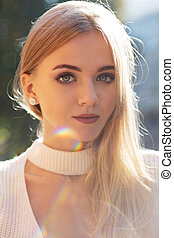 Closeup portrait of lovely blonde woman with natural makeup posing with sun glare
