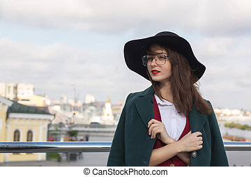 Closeup portrait of lovely brunette girl posing at the bridge. Woman wearing fashionable hat and glasses