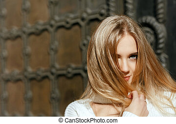 Closeup portrait of lovely model with natural makeup posing near metal wrought door. Space for text