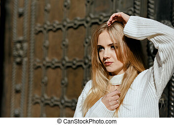 Closeup portrait of luxurious model with natural makeup posing near metal wrought door. Space for text
