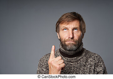 Closeup portrait of mature man in warm sweater looking up - ...