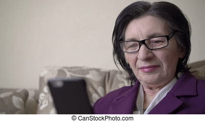 Closeup portrait of old business woman in the glasses using phone