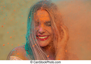 Closeup portrait of positive blonde model with red lips playing with orange and blue dry paint Holi at the desert