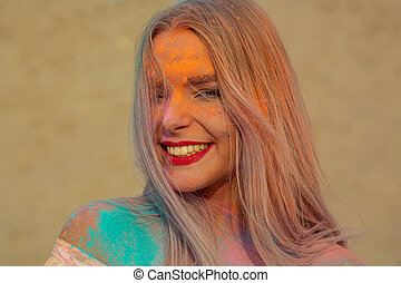 Closeup portrait of positive blonde model with red lips playing with orange dry paint Holi at the desert
