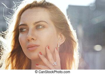 Closeup portrait of pretty blonde girl with long hair posing at the background of city. Empty space
