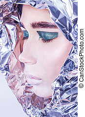Closeup portrait of pretty woman wrapped in foil looking forward standing on light grey background