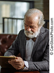 closeup portrait of retired man in formal clothes playing games on the tablet