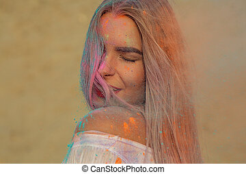 Closeup portrait of sensual blonde model with red lips playing with orange dry paint Holi at the desert