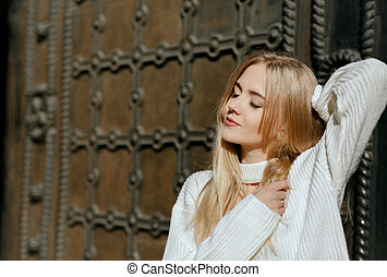 Closeup portrait of sensual girl with natural makeup posing near metal wrought door. Space for text