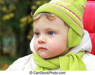 Closeup portrait of serious baby looking in hat and scarf on autumn background