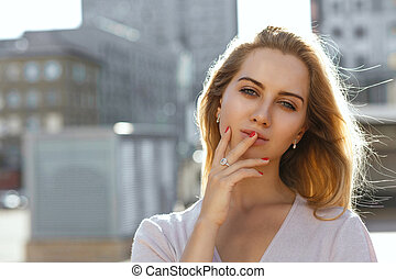 Closeup portrait of sexy blonde girl with long hair posing at the background of city. Space for text