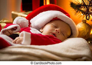portrait of sleeping baby boy in Santa cap at living room