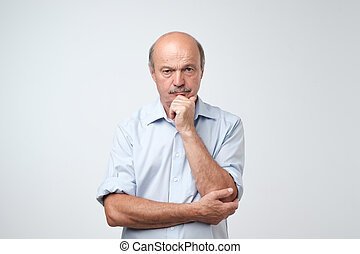 Closeup portrait of sleepy mature man in blue shirt, funny guy placing head on hand, unhappy looking at camera.
