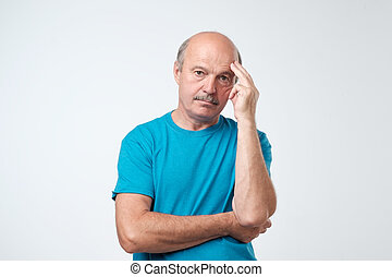 Closeup portrait of sleepy mature man in blue t-shirt, funny guy placing head on hand, unhappy looking at camera.