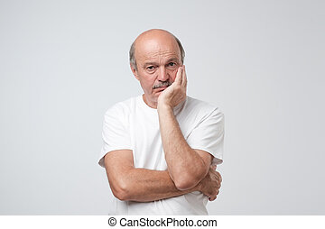 Closeup portrait of sleepy mature man in white t-shirt, funny guy placing head on hand, unhappy looking at camera.